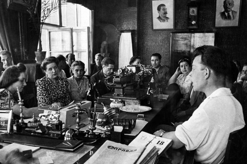 Black and white photo showing people seated around a table with newspaper Pravda in the foreground and portraits of Stalin and Lenin on wall