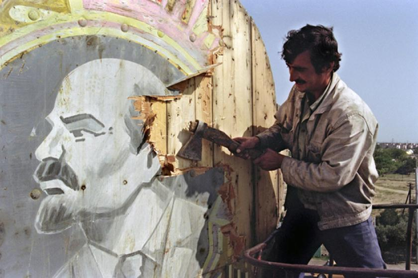 Man removes image of Lenin with axe.