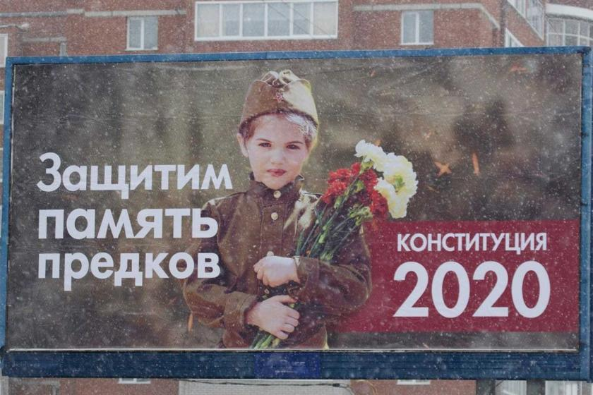 "Billboard showing young girl in World War II uniform with bouquet and inscription in Russian, ""We will defend the memory of our ancestors. Constitution 2020."""