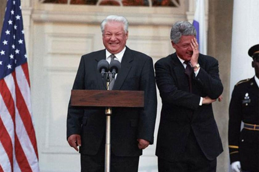 Boris Yeltsin standing at podium while Bill Clinton looks on with hand on his face